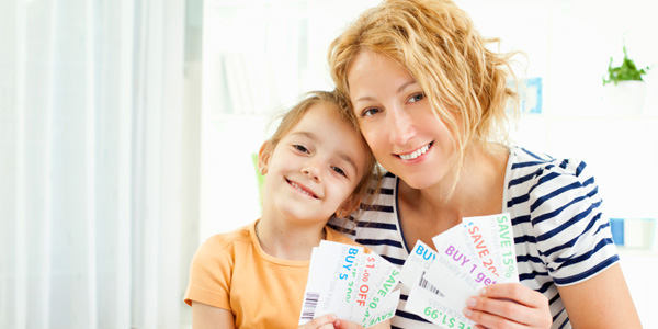 mom and daughter clipping coupons