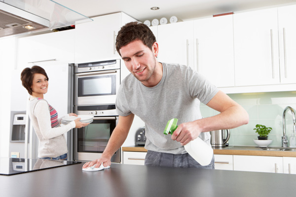 Young couple working together to clean their kitchen