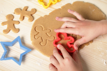 Child cutting dough with cookie cutter