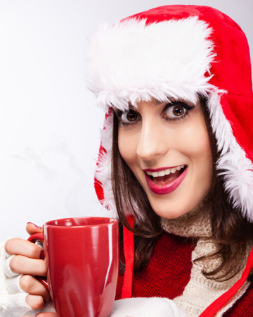 Woman drinking coffee in Santa hat