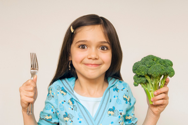 A little girl holding up her fork and broccoli