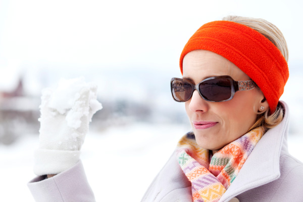 Woman wearing sunglases while playing in the snow