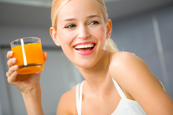 Youg woman drinkin a small glass of juice
