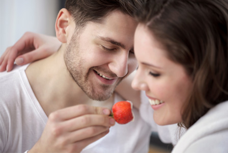 Couple feeding each other strawberries