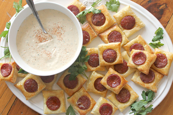 Chorizo in puff pastry squares with creamy, tangy white bean dip