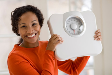 Happy woman holding scale