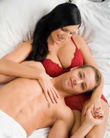 Woman wearing lingerie and laying in bed with man
