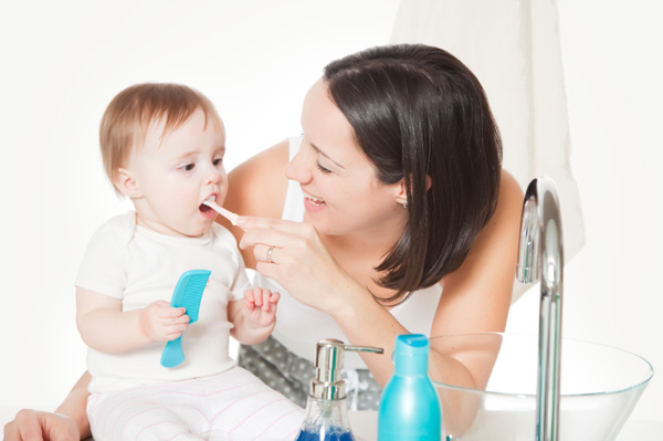 Mom brushing her baby's teeth