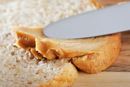 Peanut butter being spread on sandwich