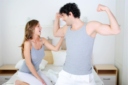 Woman feeling her boyfriend's muscle