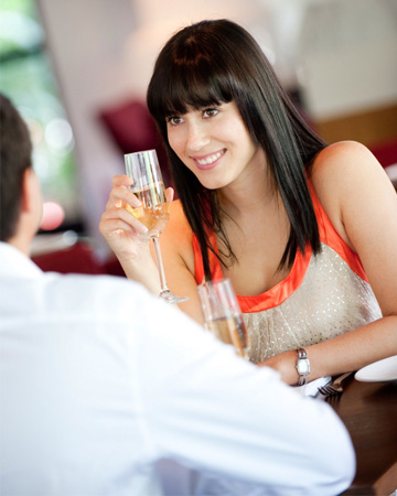 Woman having champagne dinner with man