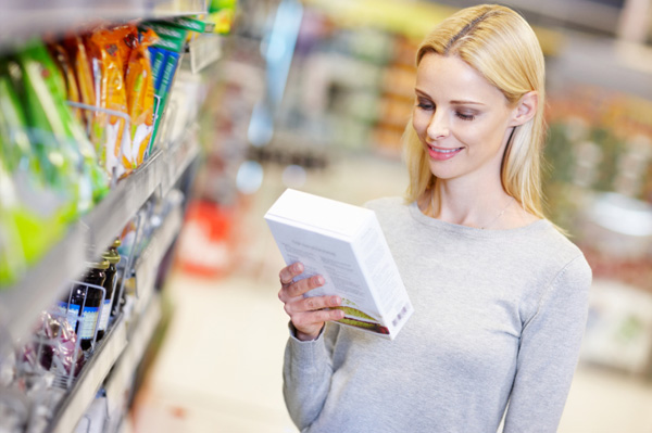Woman reading food label it supermarket