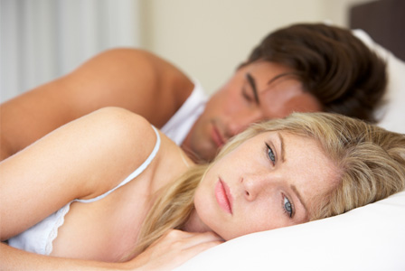 Worried woman in bed with boyfriend