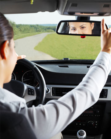 Woman adjusting rearview mirror