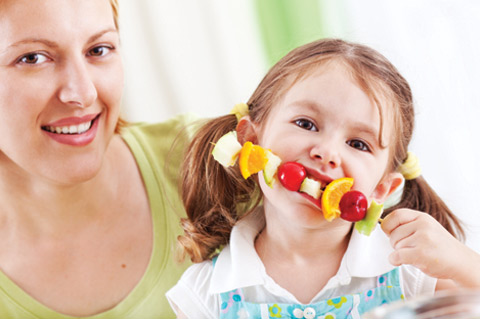 Mom with daughter eating fruit