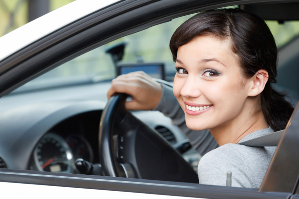 Smiling and confident young woman sitting in car
