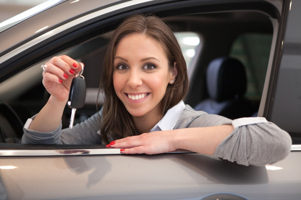 Woman holding up the keys to her new car