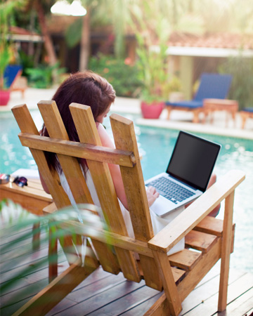 Woman working on computer at pool