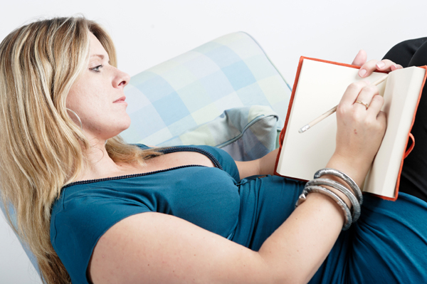 Woman writing in a pregnancy journal