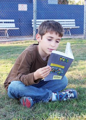 Simon reading outdoors
