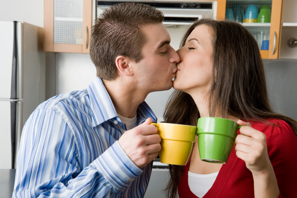 Couple kissing while clinking coffee cups