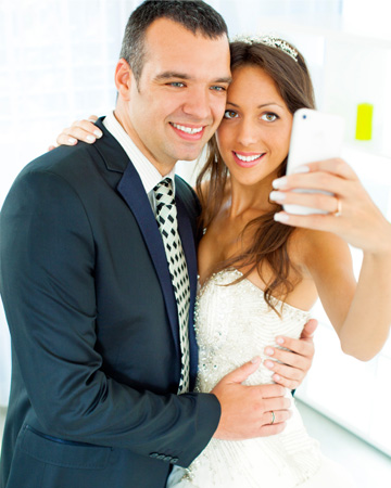 Couple using smartphone on wedding day