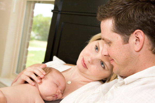Couple in bed with newborn baby