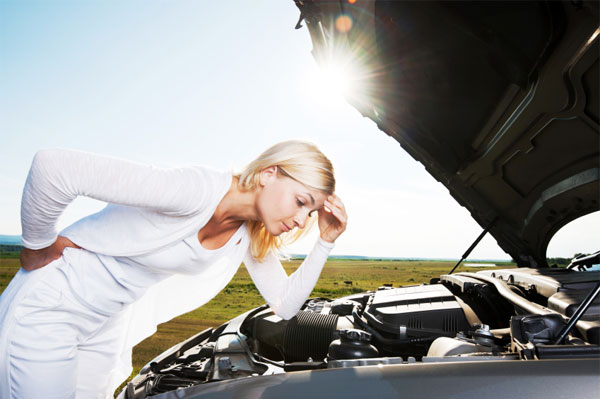 woman looking under hood of broken car