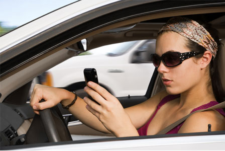 young woman driving and texting