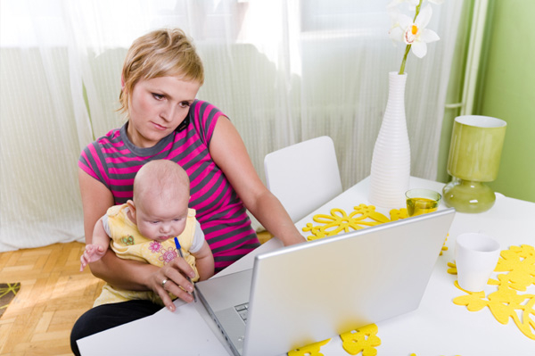 Mom on computer and phone with baby on her lap