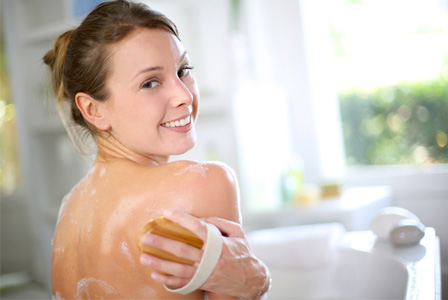 Woman exfoliating back