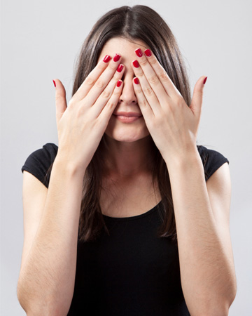 Woman hiding behind hands
