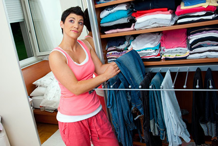 woman picking out jeans from closet