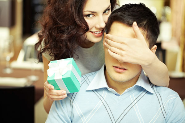 Woman giving man a small gift