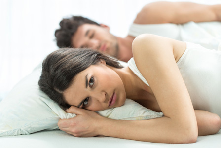 Angry woman in bed with spouse
