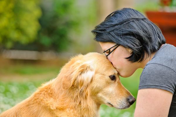 Woman kissing dog on head