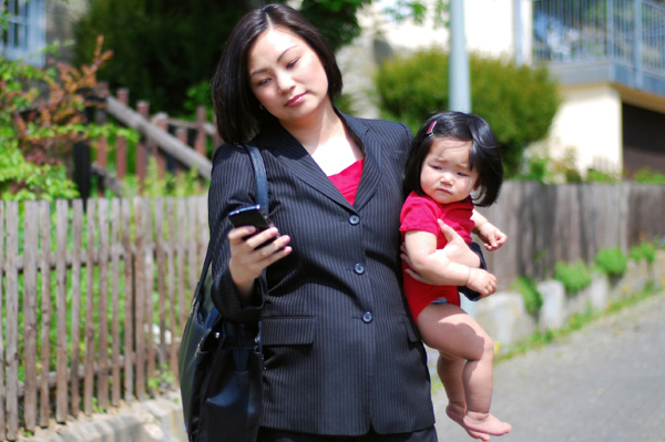 Working mom on Blackberry while holding baby