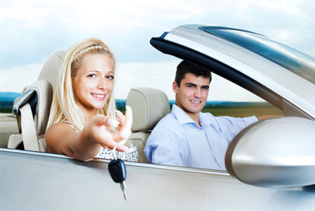 Couple in a car handing over keys