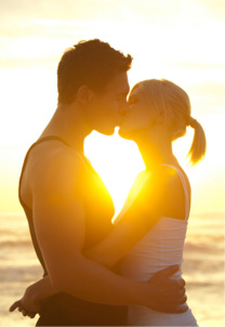 Couple kissing on beach at dusk