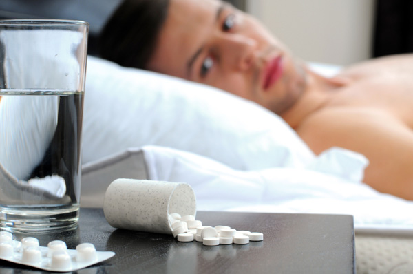 Man in bed looking at pills