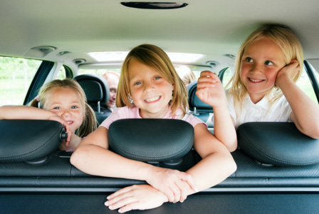 Three smiling girls looking backward from rear seat