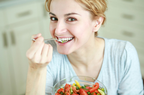 Happy woman eating vegetables