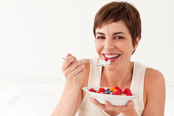 Woman eating yogurt and fruit