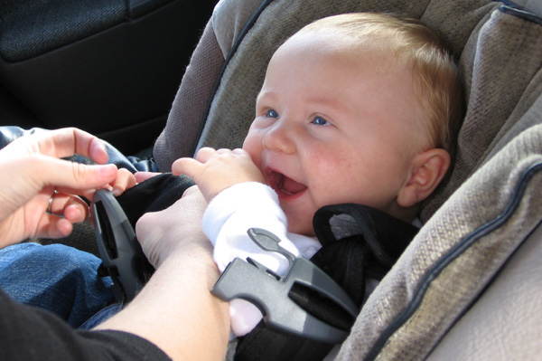 Happy baby being buckled into carseat