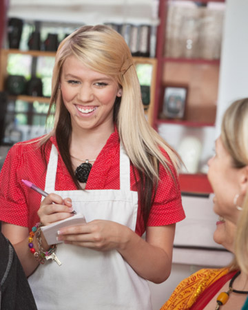 Teenage waitress taking order at table
