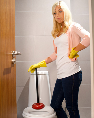 Woman dealing with clogged toilet