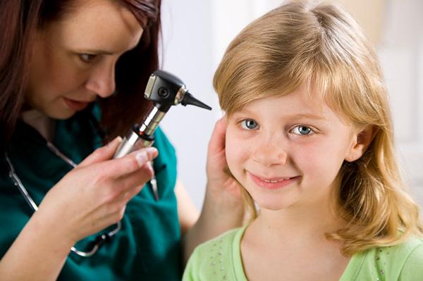 Doctor examining young girls ear