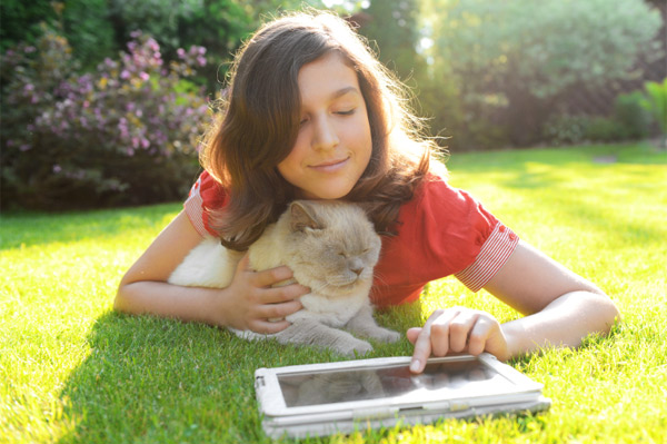 Girl with cat playing on tablet