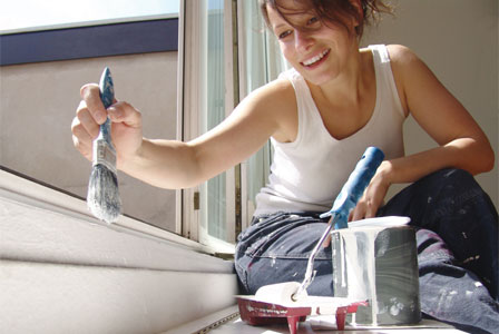 Woman painting window sill