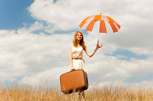 Woman holding suit case and umbrella